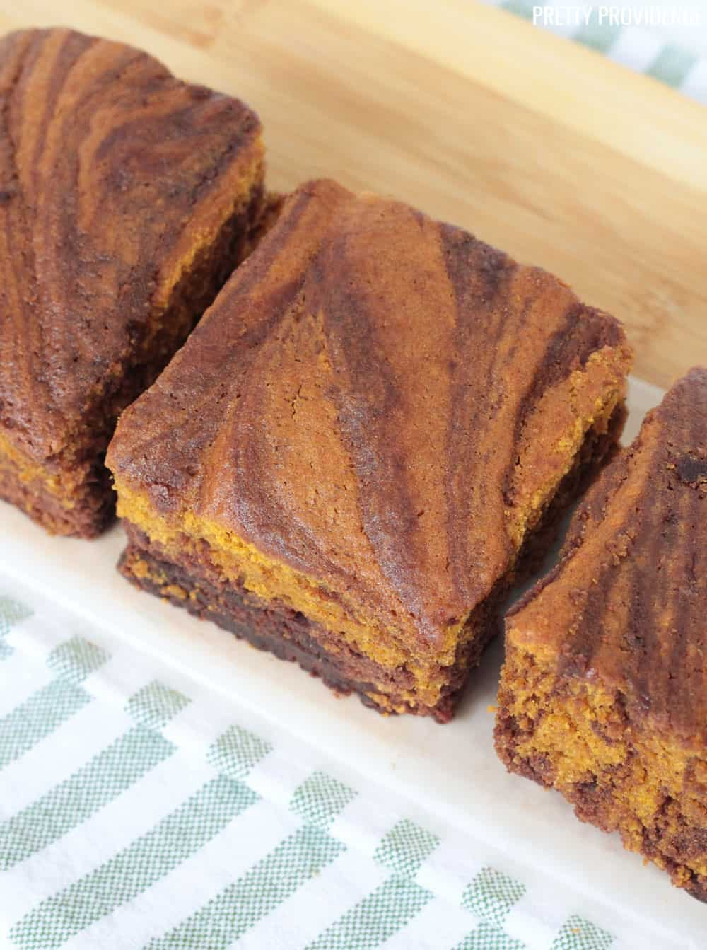 Pumpkin Brownies, three squares on a cutting board, with a green and white striped towel under it.