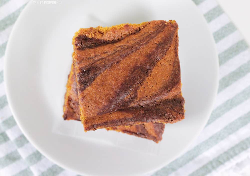 Pumpkin brownies swirled, stacked two-high with a white plate underneath.