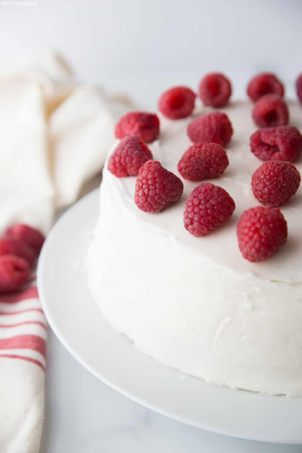 Chocolate Raspberry Cake covered in cream cheese frosting garnished with fresh raspberries on the top.