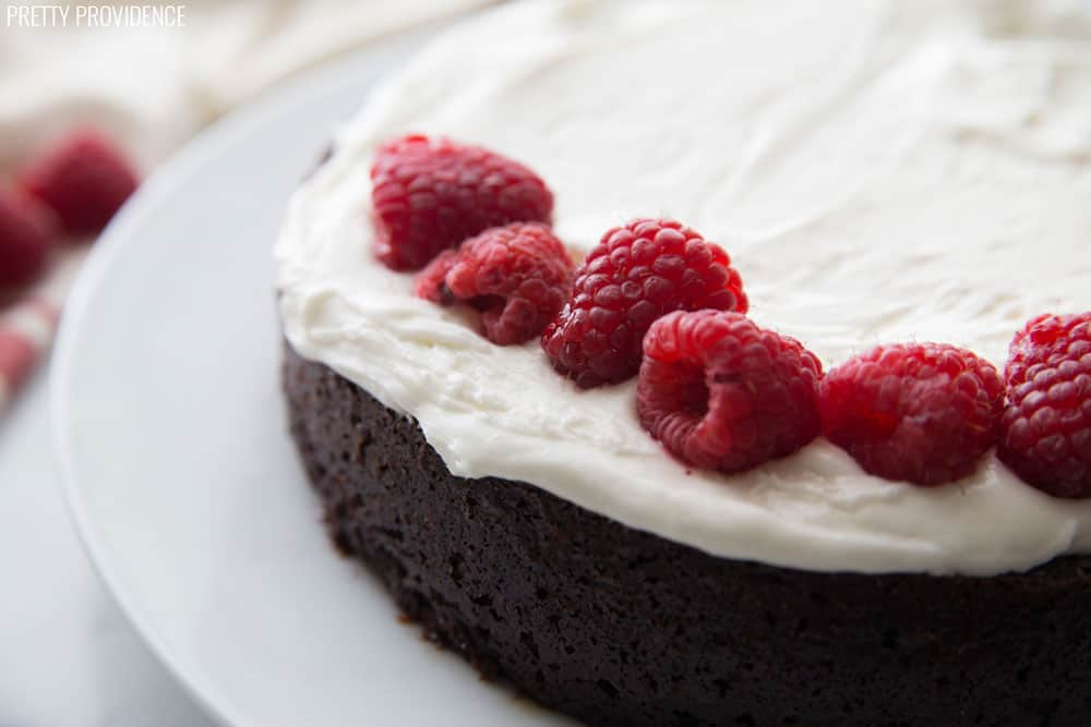 Layer of cream cheese frosting and fresh raspberries on top of a round chocolate cake.