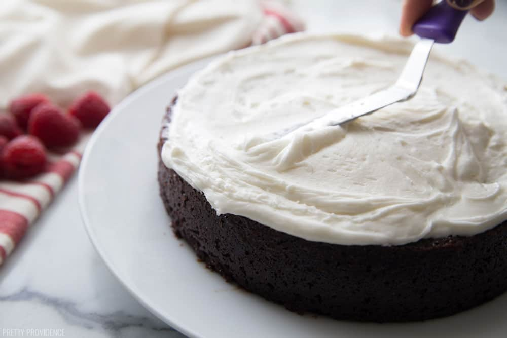 Cream cheese frosting being spread thick onto a round layer of chocolate cake using a thin spatula.
