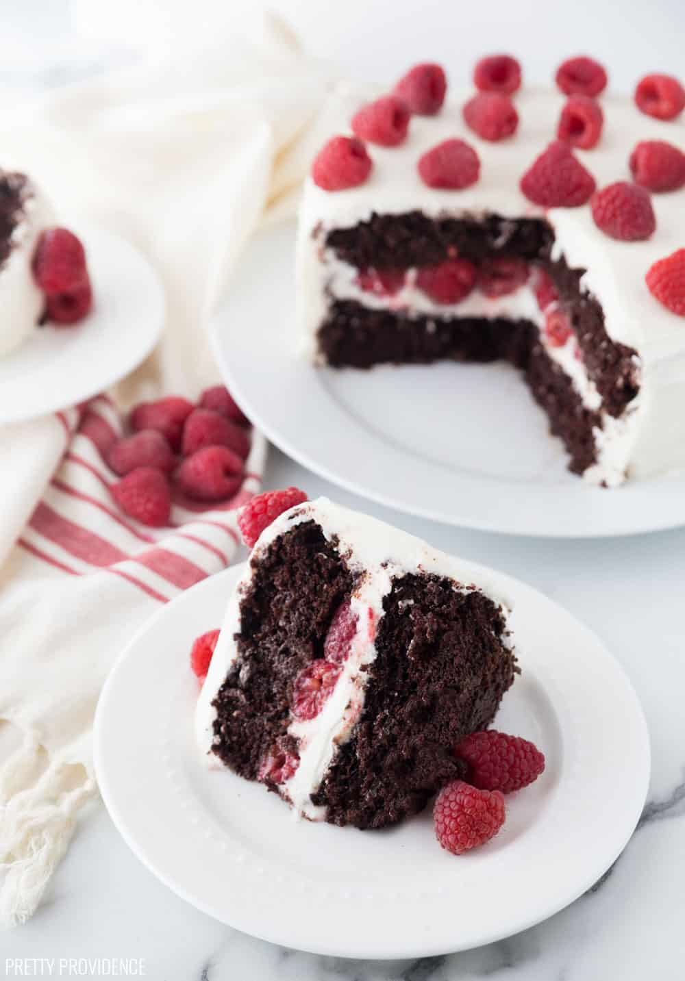 Chocolate cake with raspberries and cream cheese frosting, one slice on a cake plate with the rest of the cake in the background.