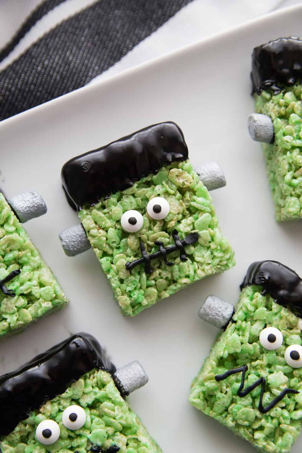 cute frankenstein rice krispie treat on a white plate and dish towel