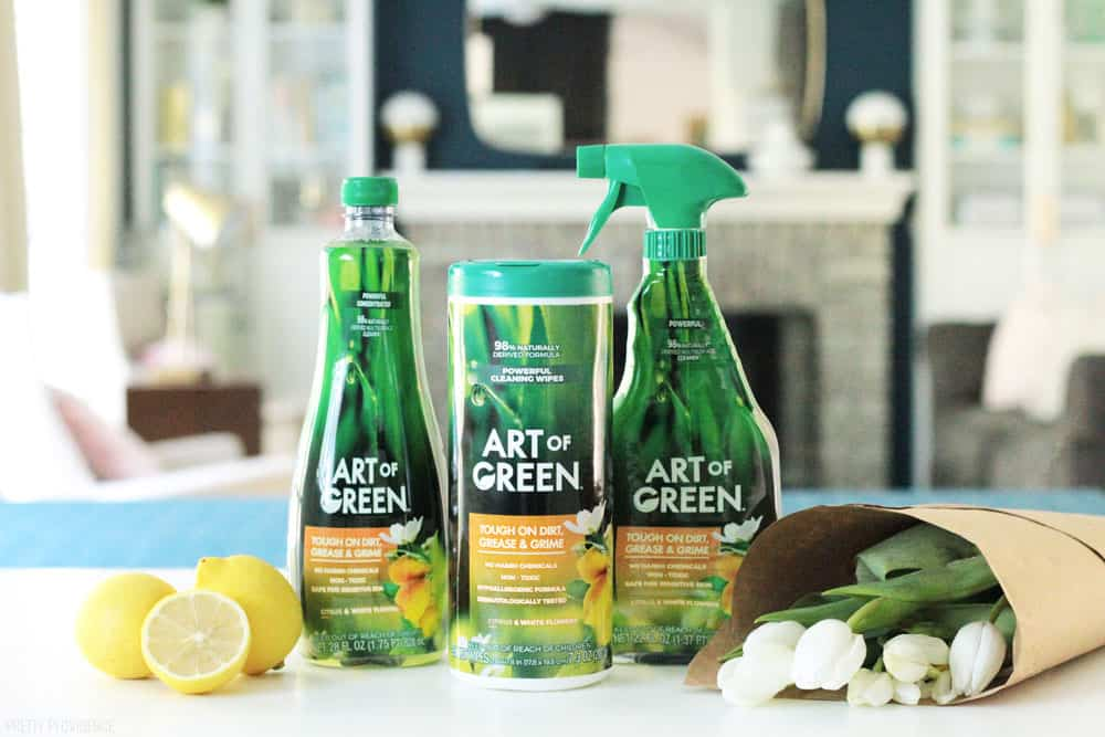 Art of Green cleaning products on a kitchen counter with fresh tulips and lemons on a white countertop.