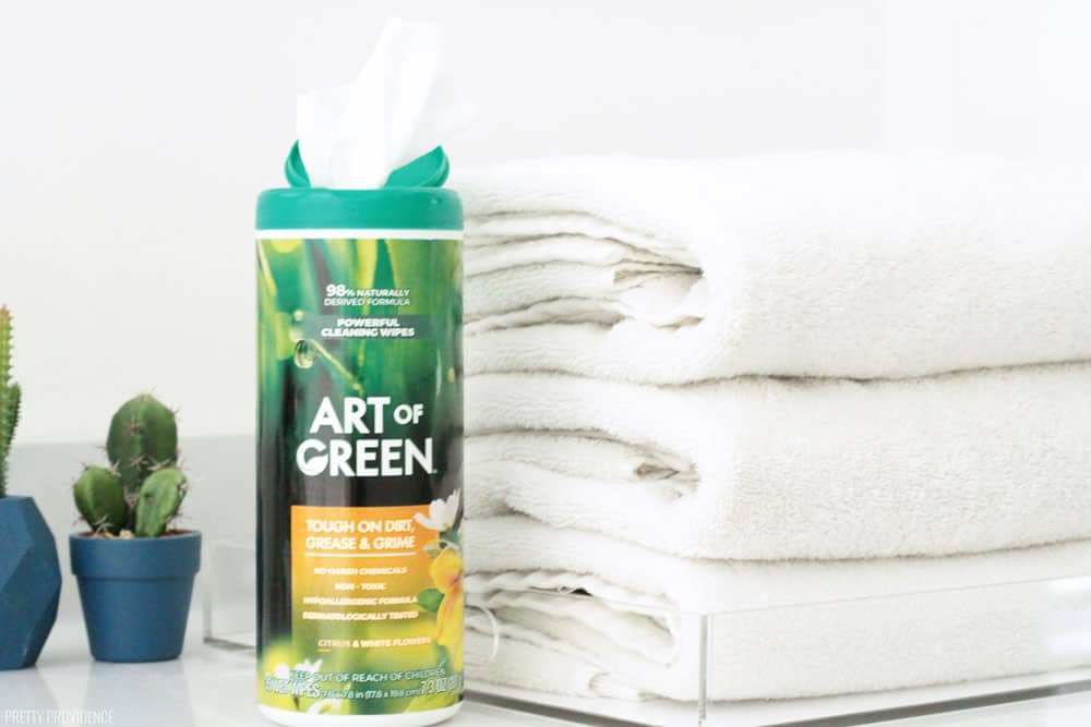 Art of Green cleaning wipes on a marble countertop with three clean white towels folded.