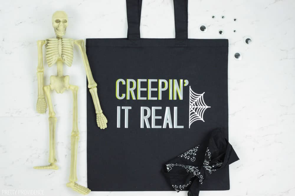 Creepin' It Real black Halloween Trick or Treat tote bag with a spiderweb on it, skeleton and googly eyes on the side.