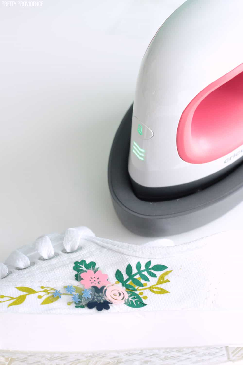EasyPress Mini (mini craft iron made by Cricut) and a white keds shoe with iron-on vinyl being applied to it.