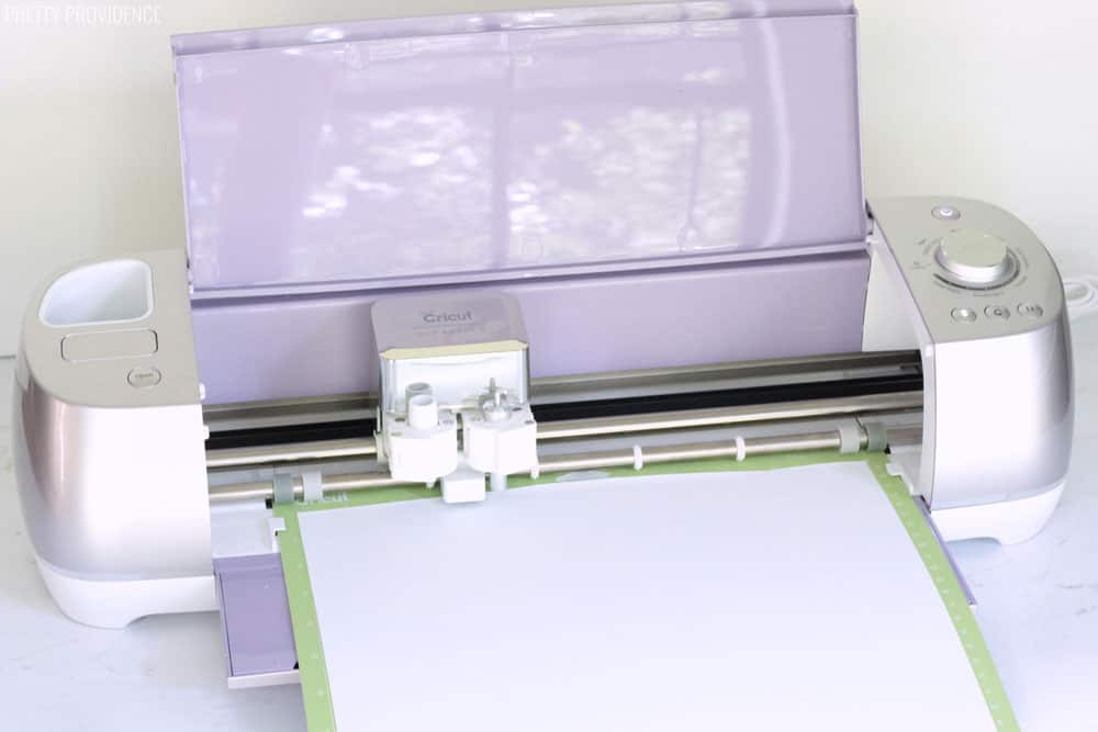 Cricut Explore Air 2 Wisteria (metallic light purple) with a StandardGrip mat and white iron-on loaded into the machine.