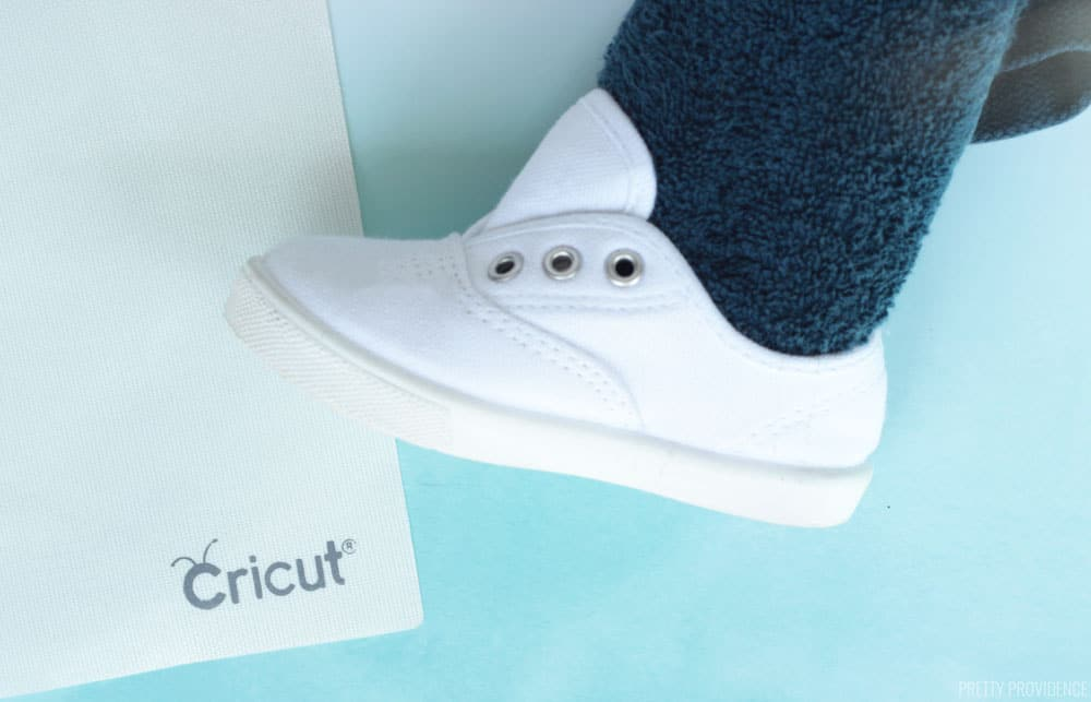 White keds toddler shoe with a towel inside and an iron-on protective sheet next to it, tutorial for EasyPress Mini instructions for applying iron-on to shoes.