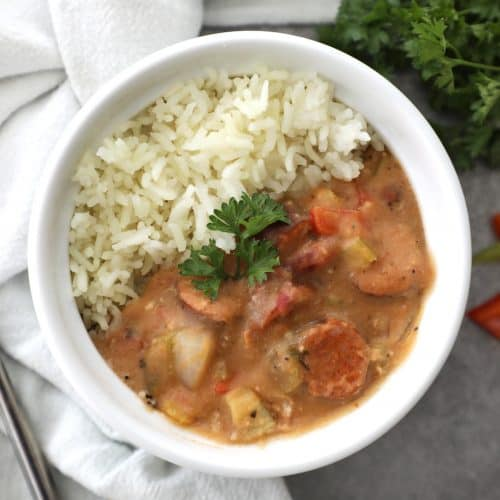 white bowl filled with gumbo and rice next to a tea towel and parsley