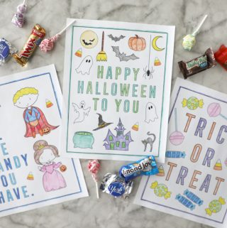 three halloween coloring pages colored in on a marble counter surrounded by candy groupings