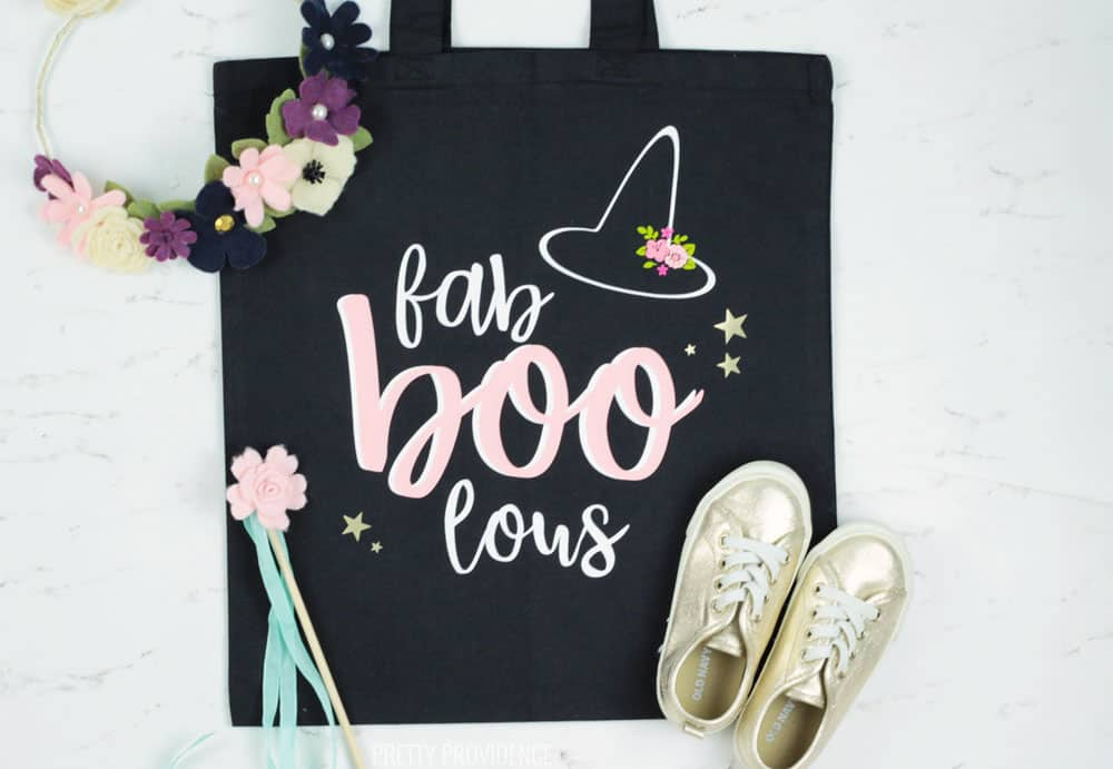 Fab-Boo-Lous Halloween Trick or Treat tote bag! Black tote bag with a floral witch hat and words in white, pink, and gold iron-on.