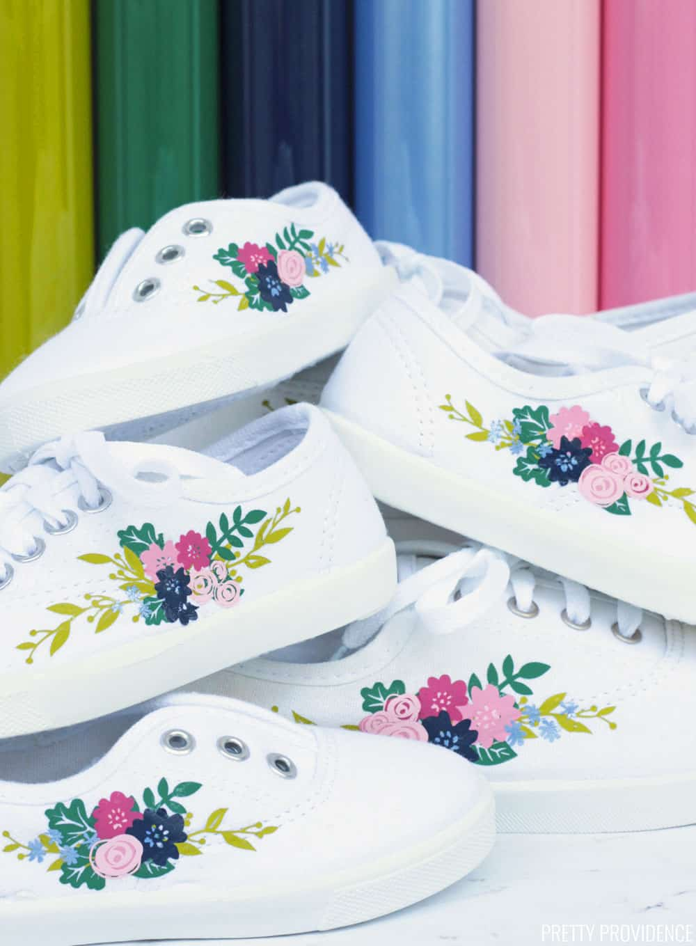Six white keds style shoes with floral iron-on designs on them, iron-on rolls behind them in the background.