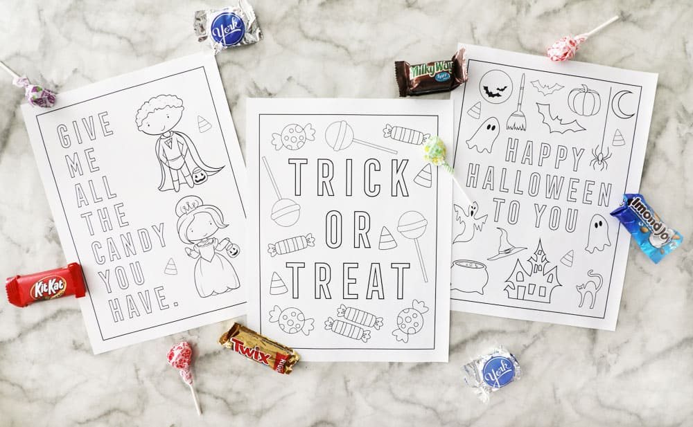 three blank halloween coloring pages on a marble counter with candy accents