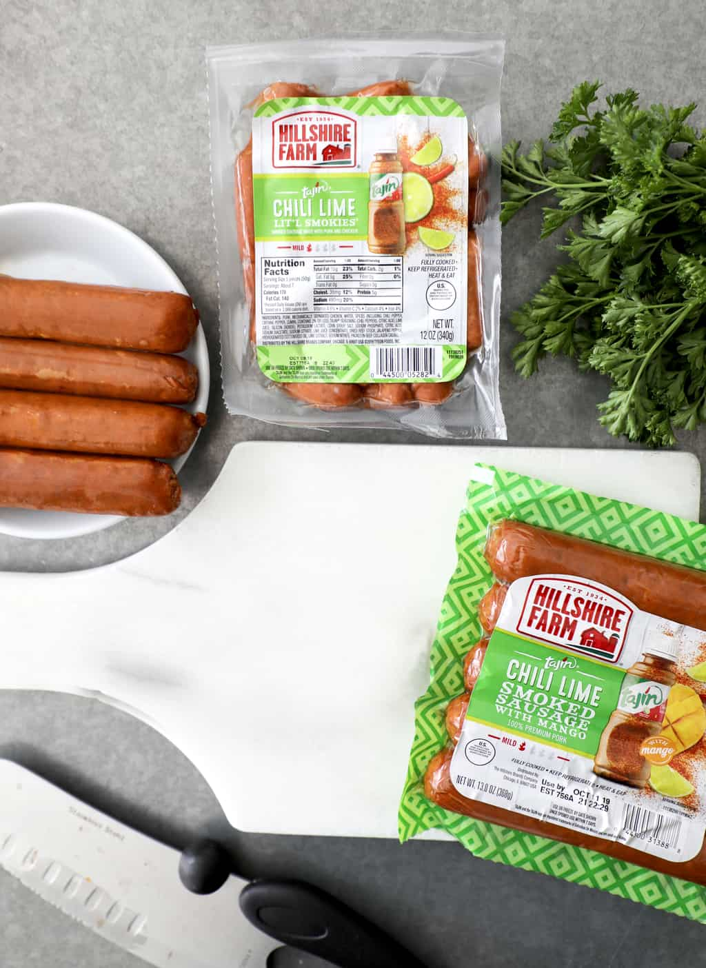 hillshire farms sausage links on a plate by a cutting board and little smokies package