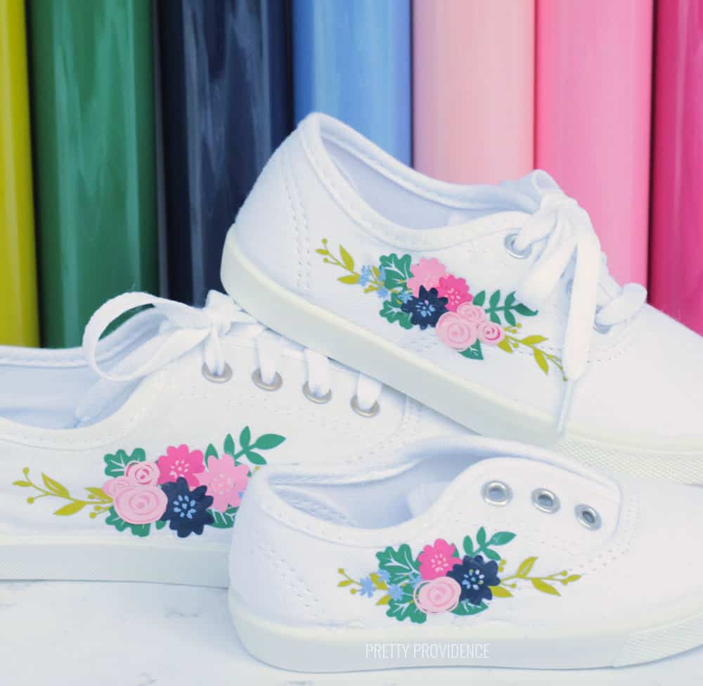 Three white shoes with floral motifs on the side, with rolls of colorful Iron On vinyl in the background.