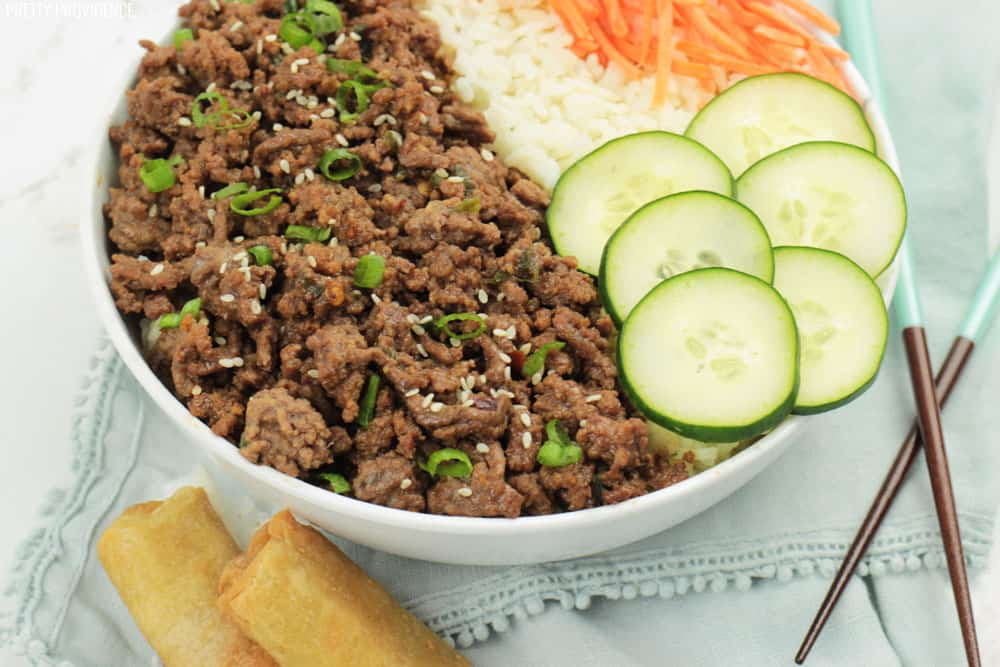 Korean beef and rice in a bowl with cucumbers, carrots on top, egg rolls on the side and chop sticks to eat with.