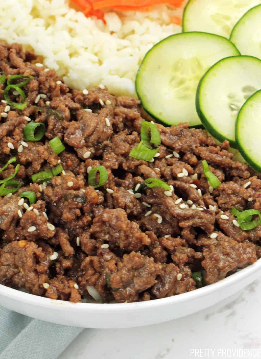 Korean Ground Beef and Rice bowl close-up with sliced cucumbers on top.