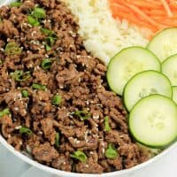 Korean Beef and rice in a bowl with green onions and sesame seeds on top, cucumbers and shredded carrots on the side.