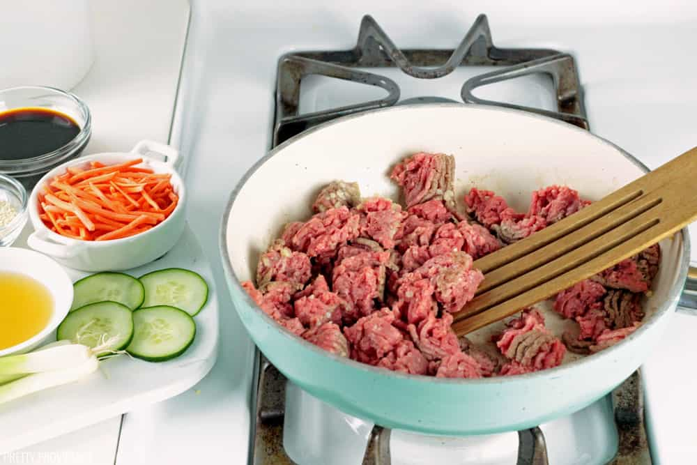 Lean ground beef being browned in a non-stick pan, with other Korean Beef ingredients off to the side.