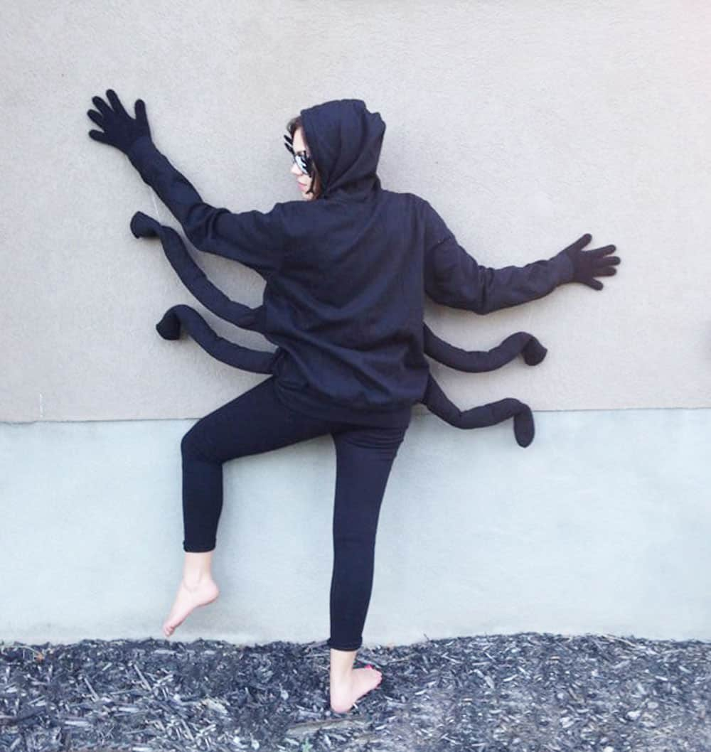 an adult woman in a spider costume against the side of a house