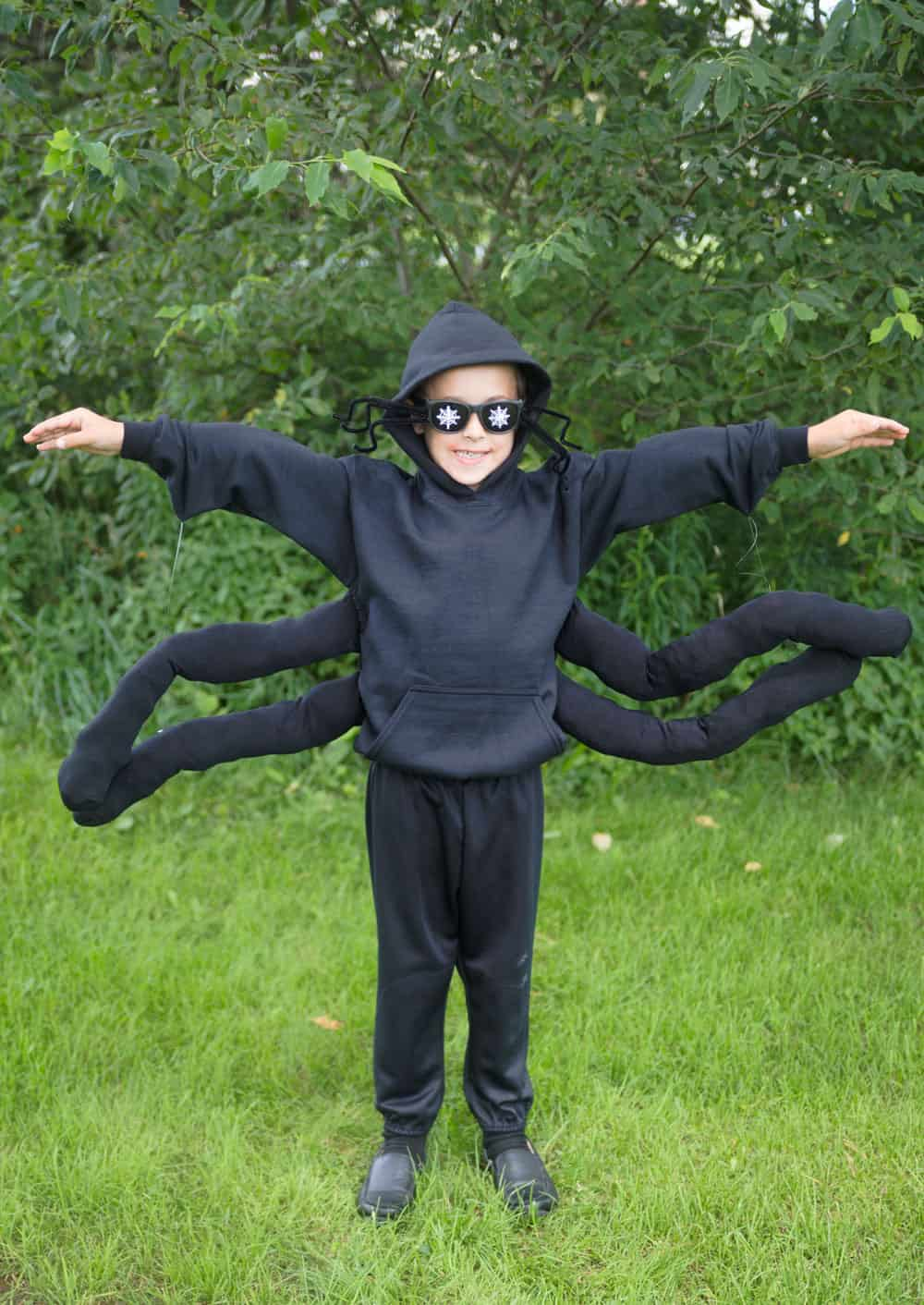 young boy in a spider costume against green grass and green trees