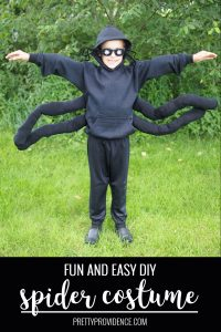 toddler spider costume against a green foresty background