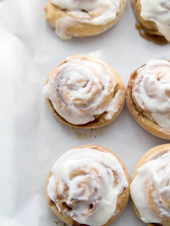 freshly frosted cinnamon rolls on a wax paper covered cookie sheet