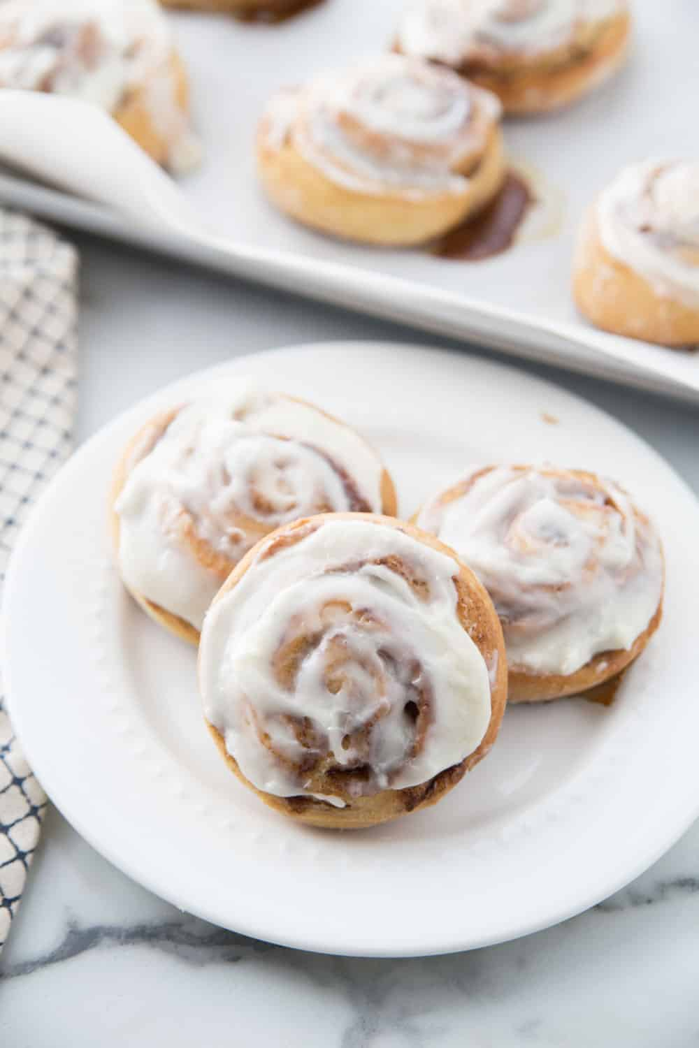 three cinnamon rolls on a white plate with the pan in the back ground