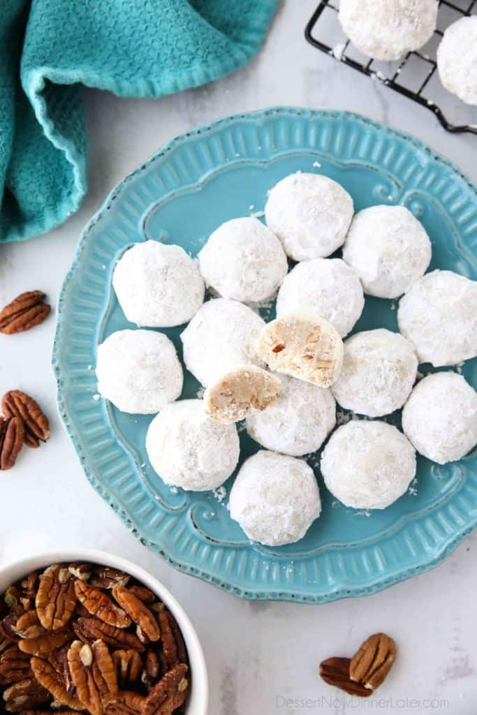 Snowball cookies on a blue plate with pecans on a plate