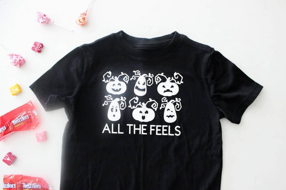 t-shirt halloween noir avec des lanternes jack o blanches faisant différentes expressions faciales