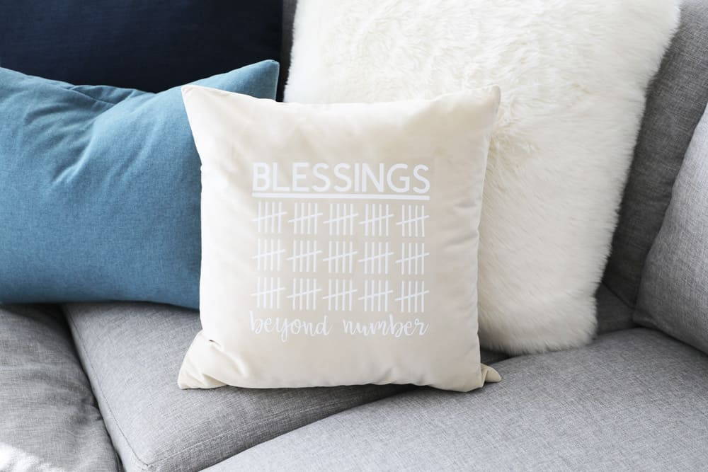 blessings beyond number pillow on a sectional surrounded by other pillows