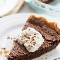 Slice of Chocolate Chess Pie topped with whipped cream on a white plate.