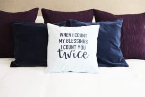 count you twice light blue pillow on a bed in front of two navy and three purple pillows