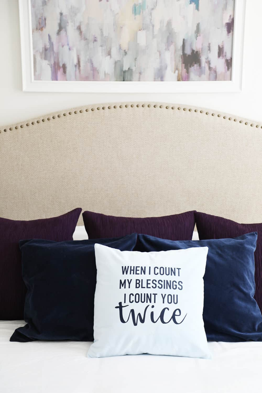 count you twice fall pillow on bed in front of two navy and three purple pillows