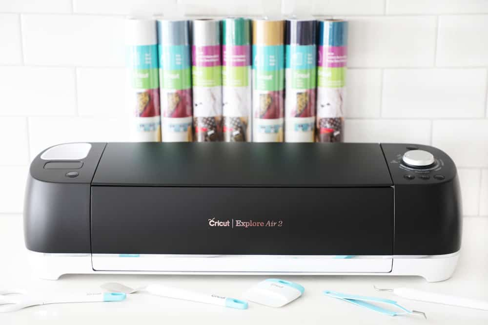 a black cricut machine on a white counter with colorful rolls of vinyl arrayed behind it