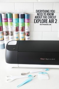 a black cricut machine with vinyl behind it and tools in front on a white kitchen counter