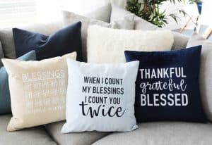 three cute fall pillow designs on a greige sectional with a plant behind them