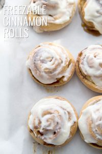 freshly frosted cinnamon rolls on a wax paper lined tray