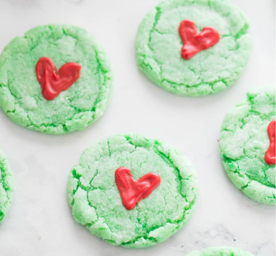 Grinch cookies - green sugar cookies with red icing hearts on them