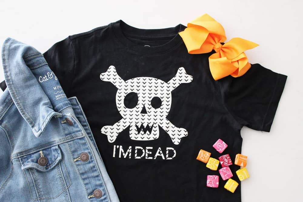 I'm Dead Halloween T-shirt featuring a skull and crossbones, with orange bow, starburst and a denim jacket.