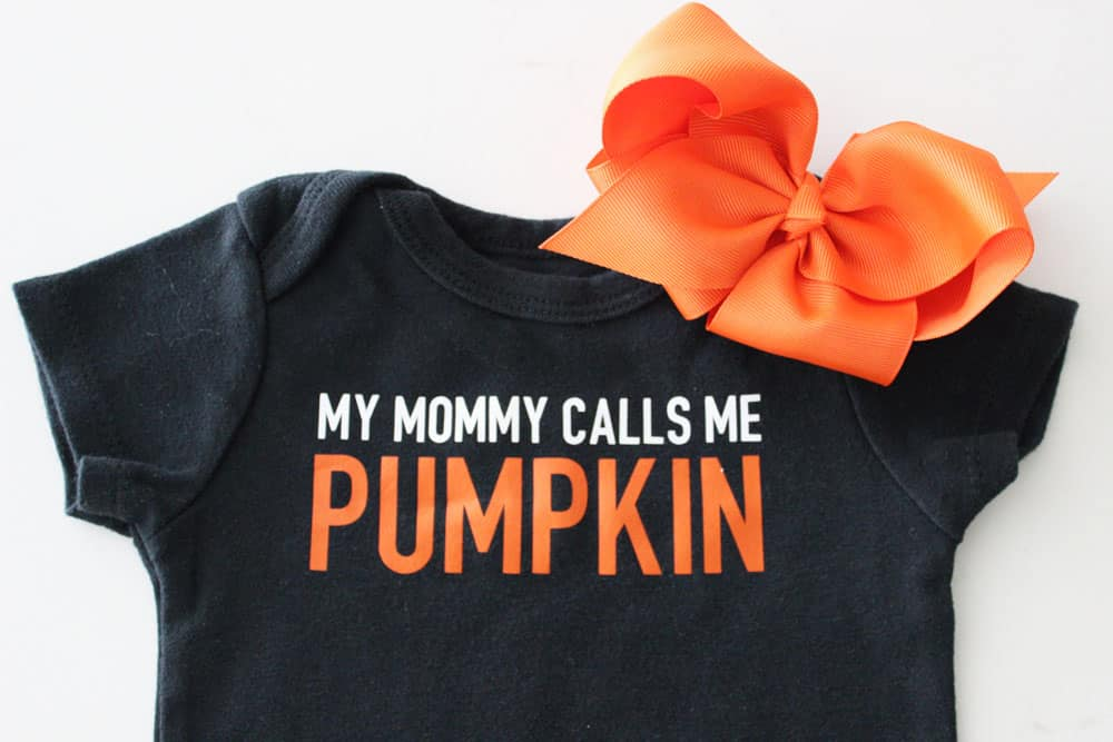 black onesie that says my mommy calls me pumpkin with an orange bow