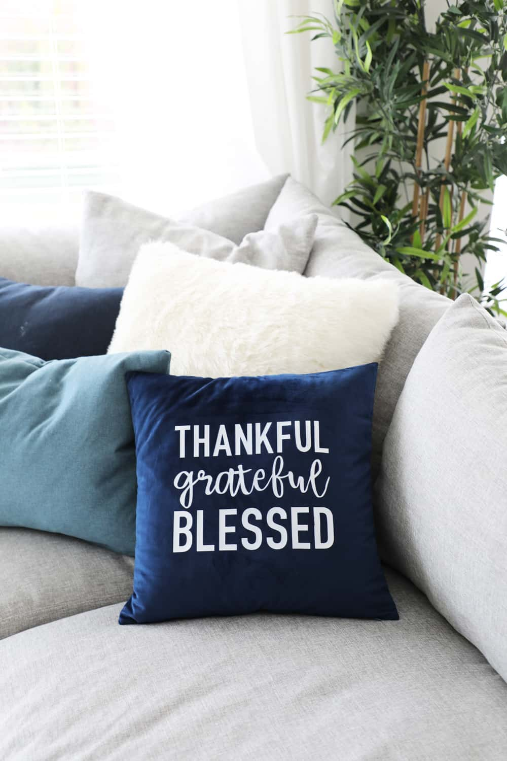 thankful grateful blessed fall pillow on a cozy sectional with other pillows