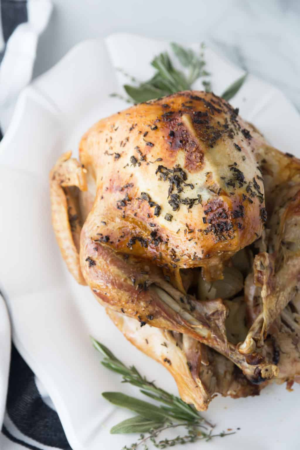 finished Thanksgiving Turkey on a white platter on a granite counter with herbs as garnish