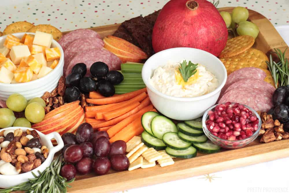 Appetizer board with vegetables, apple slices, grapes, pomegranate seeds, veggie dip, crackers and cheese cubes.