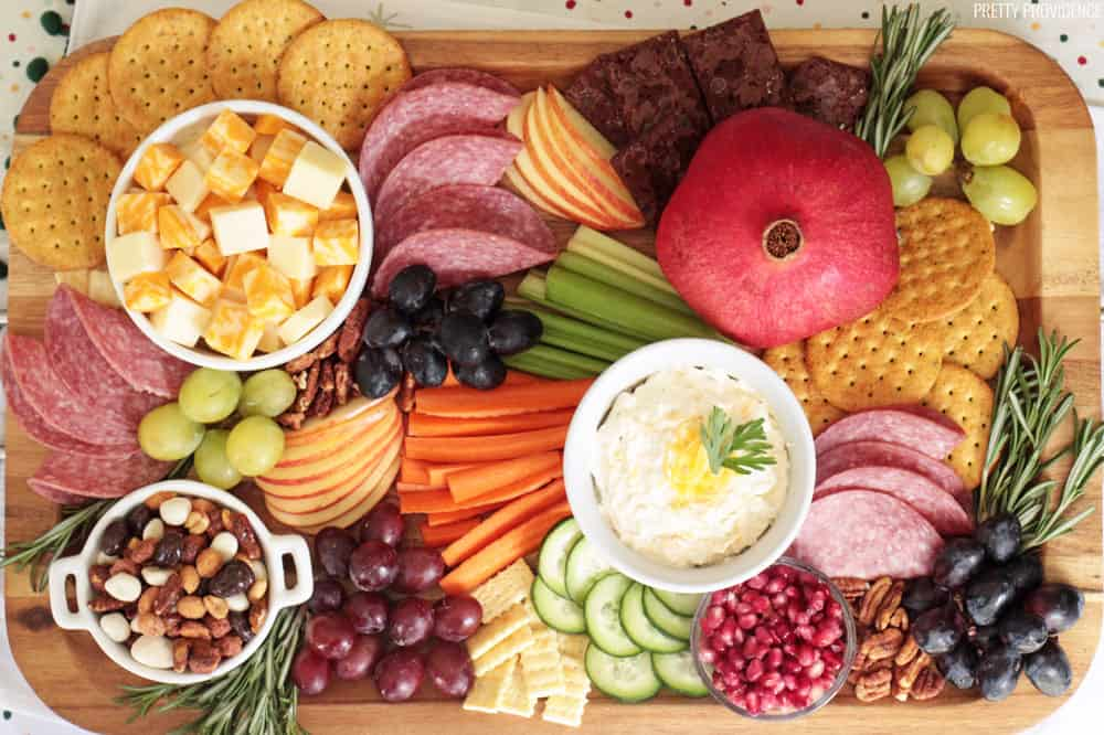 Appetizer board with fruit, cheese, meat, crackers and vegetables.