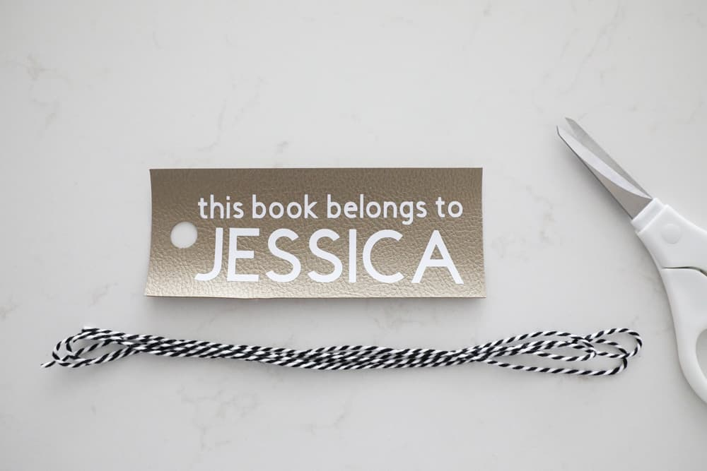bookmark next to white scissors and black and white bakers twine