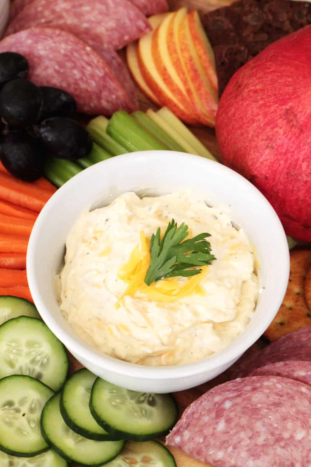 Cream Cheese Veggie Dip in a white bowl with garnish surrounded by cucumbers, carrots, celery, salami, apples and grapes.