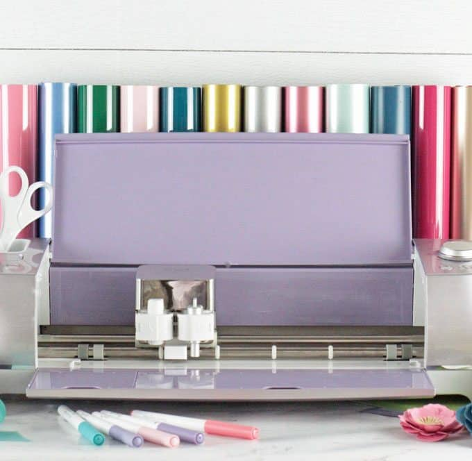 Light purple Cricut Explore Air 2 Machine with cricut accessories around it. EasyPress Mini, EasyPress 2, Cricut pens and rolls of vinyl.