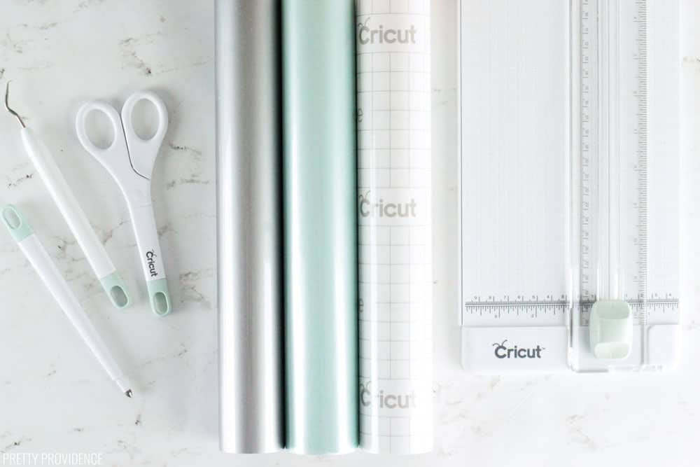 Cricut Accessories and tools you need - scissors, weeding tool, vinyl in silver, mint, transfer tape, and a paper cutter.